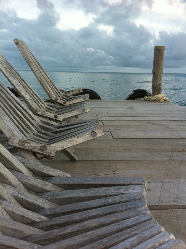 Chairs on the dock of Wee Wee Caye Marine Lab in Belize by Joshua Armagost