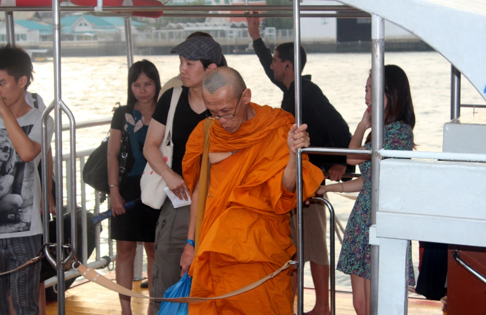 A Buddist monk steps out from a river taxi at the Temple of Dawn in Bangkok, Thailand by Max Popour